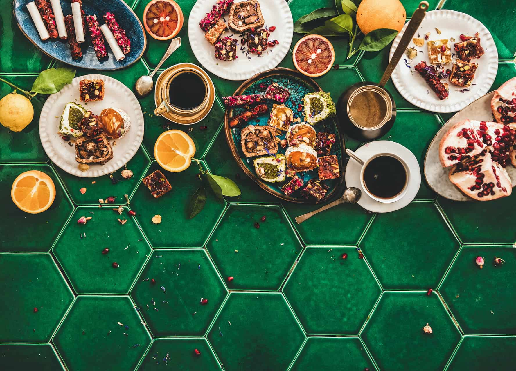 Flat-lay of variety of Turkish traditional lokum sweet delight with Turkish coffee in cups and fresh fruits over green Moroccan tile table, top view, copy space. Middle East typical dessert food